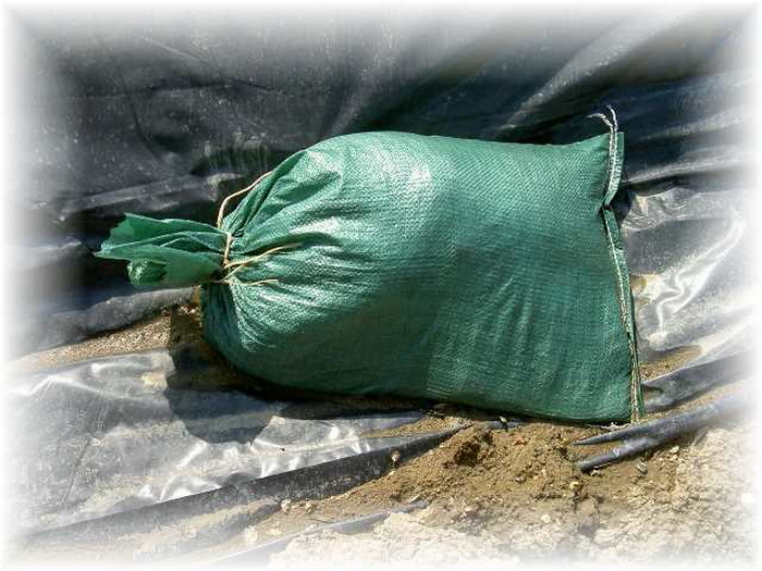 green sandbag on black plastic tarp