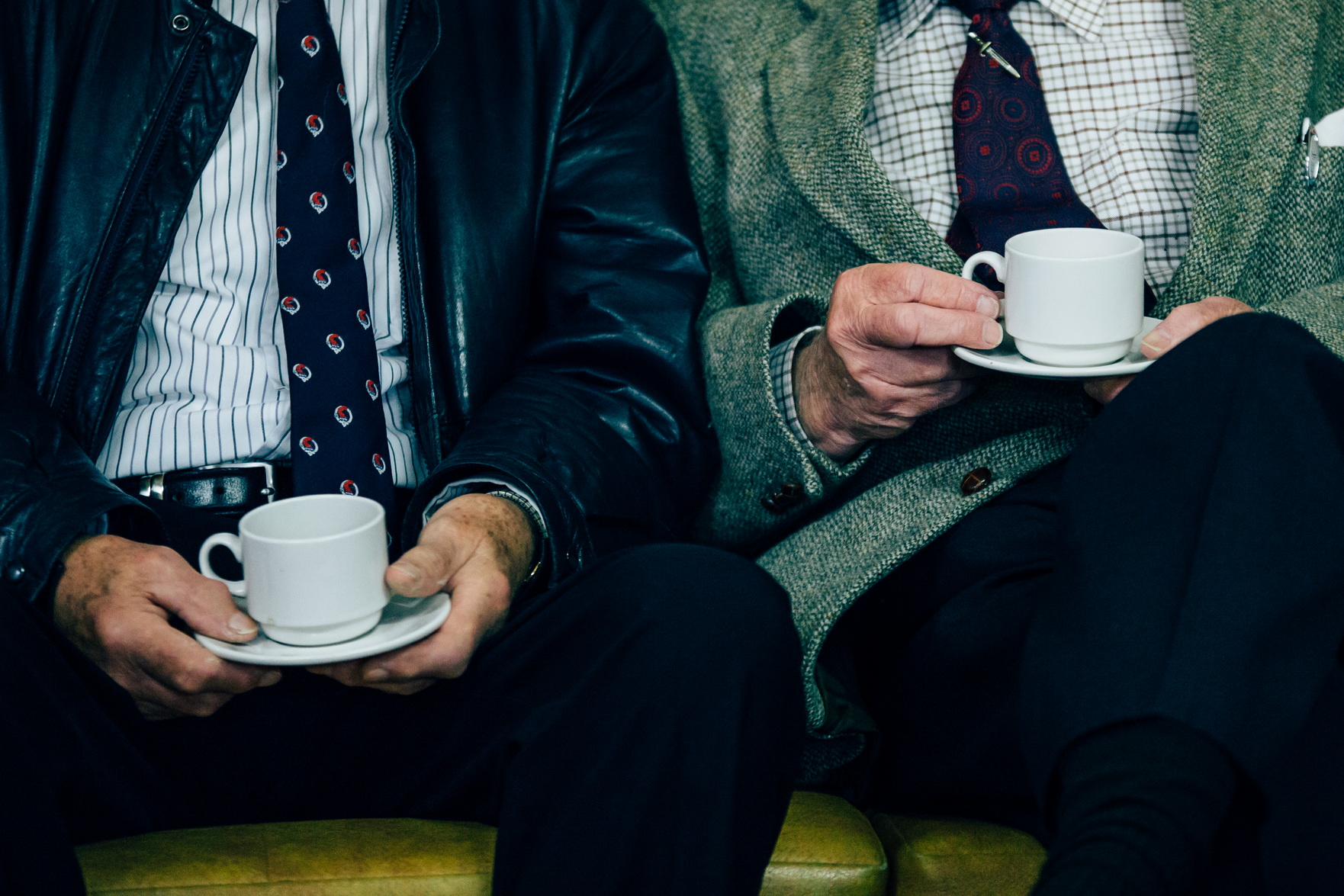 two old men on a bench drinking coffee