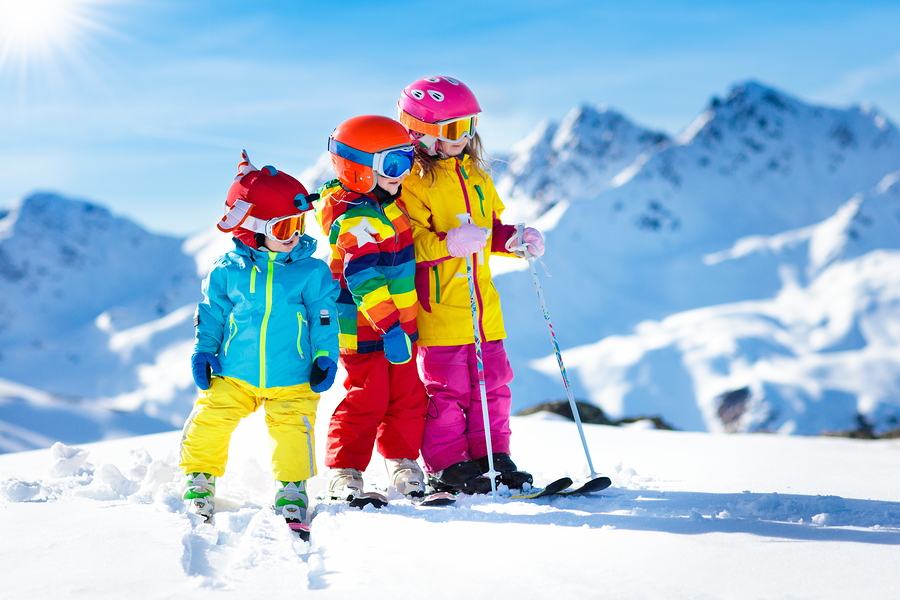 brightly dressed kids on ski hill