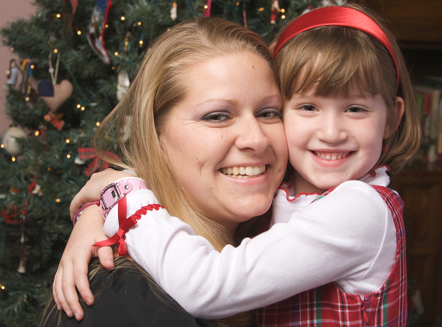 woman hugging a child by Christmas tree